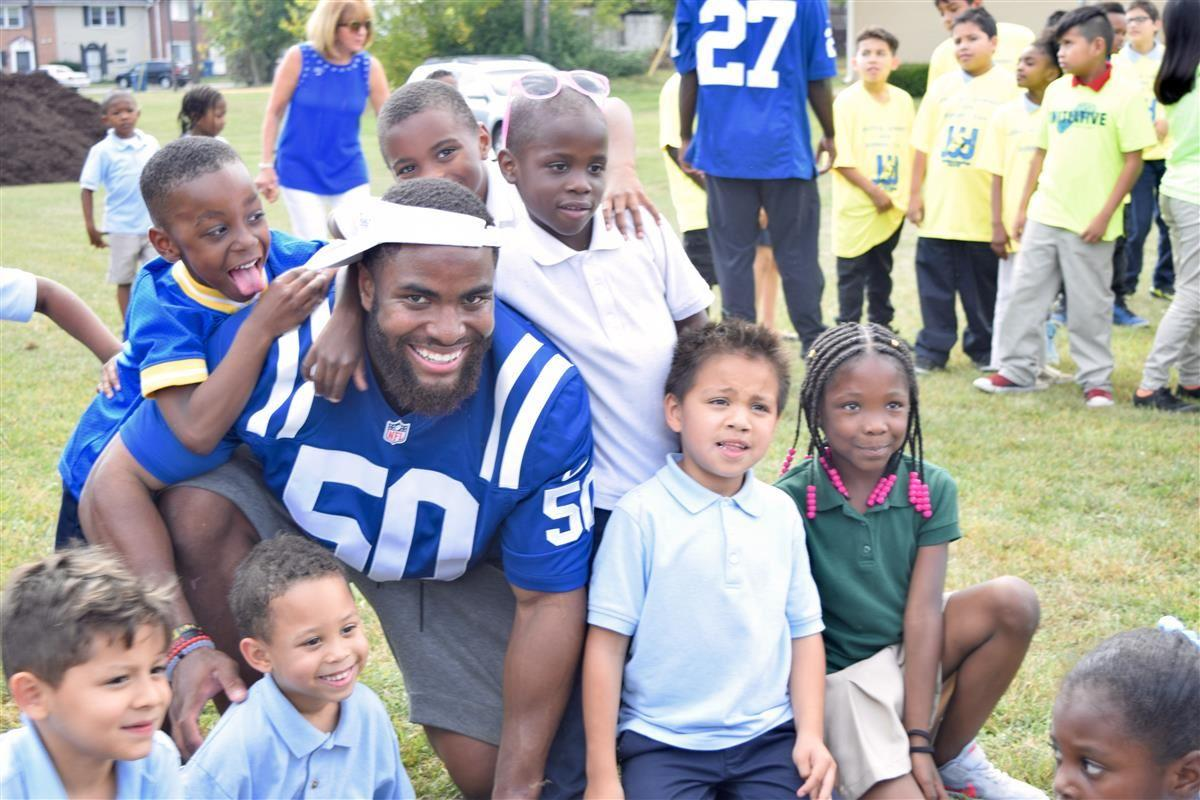 Students with a Colts player at School 109's playground build
