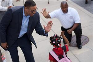 Dr. Ferebee high fives a student on the first day of school