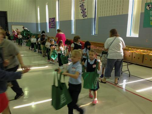 Students at Daniel Webster School 46 go through an assembly line for back-to-school supplies from Kroger.