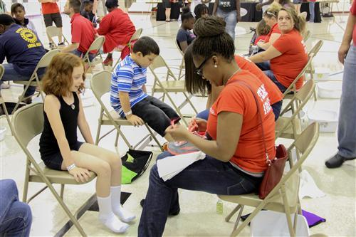 An Indiana Members Credit Union volunteer assists a Riverside School 44 student with new sneakers.