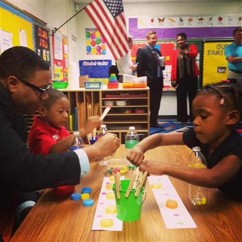 Superintendent Dr. Lewis D. Ferebee works with pre-school students at Eliza Blaker School 55