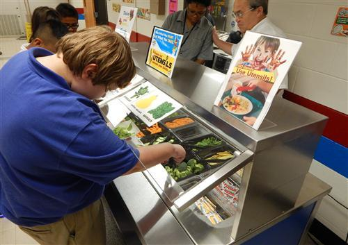 A student at SUPER School 19 helps himself to the school's new salad bar.