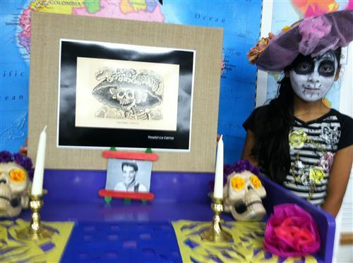 """A student from George Julian School 57 stands with the """"Ofrenda"""" the school created for Dia de los Muertos."""