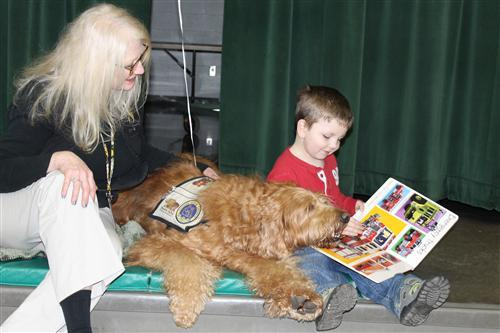 Eleanor Skillen student reading to a Paws and Think therapy dog.