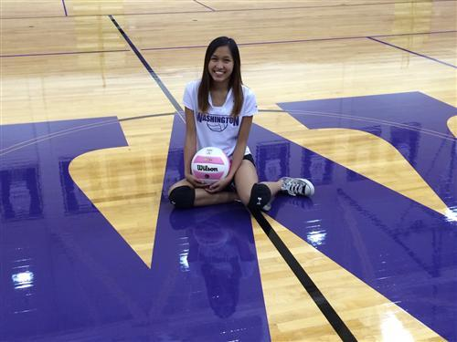 July Moe from George Washington Community High School poses on the gym floor with a volleyball.